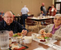 Two individuals enjoying lunch in a Meals on Wheels Dining Room.