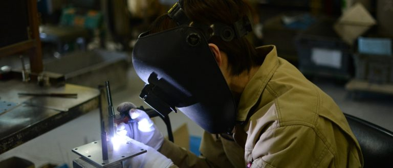 A welder working on machinery in a factory.