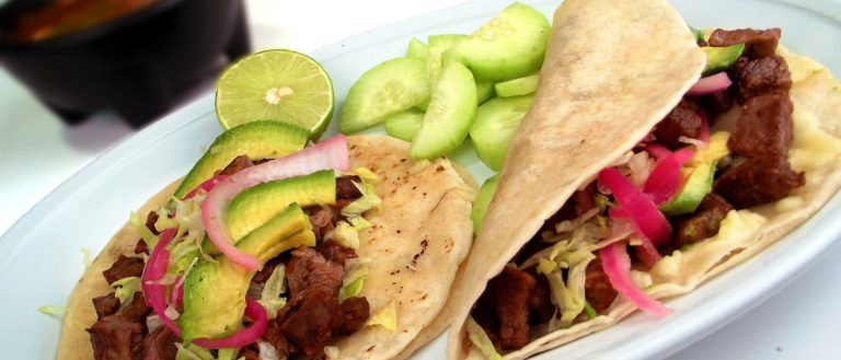 Al pastor tacos on a plate with limes.