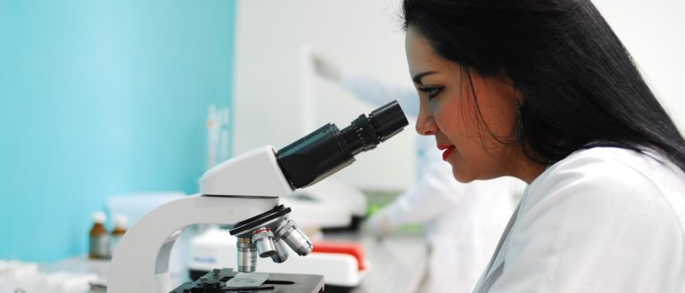A lab worker examining a specimen with a microscope.